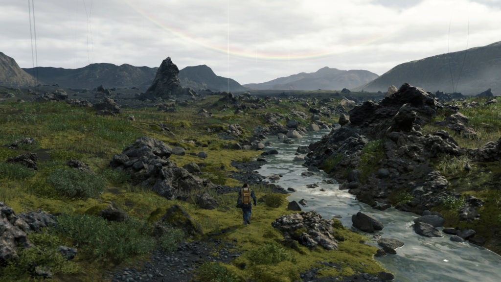 Death Stranding: Norman Reedus walking next to river in futuristic landscape